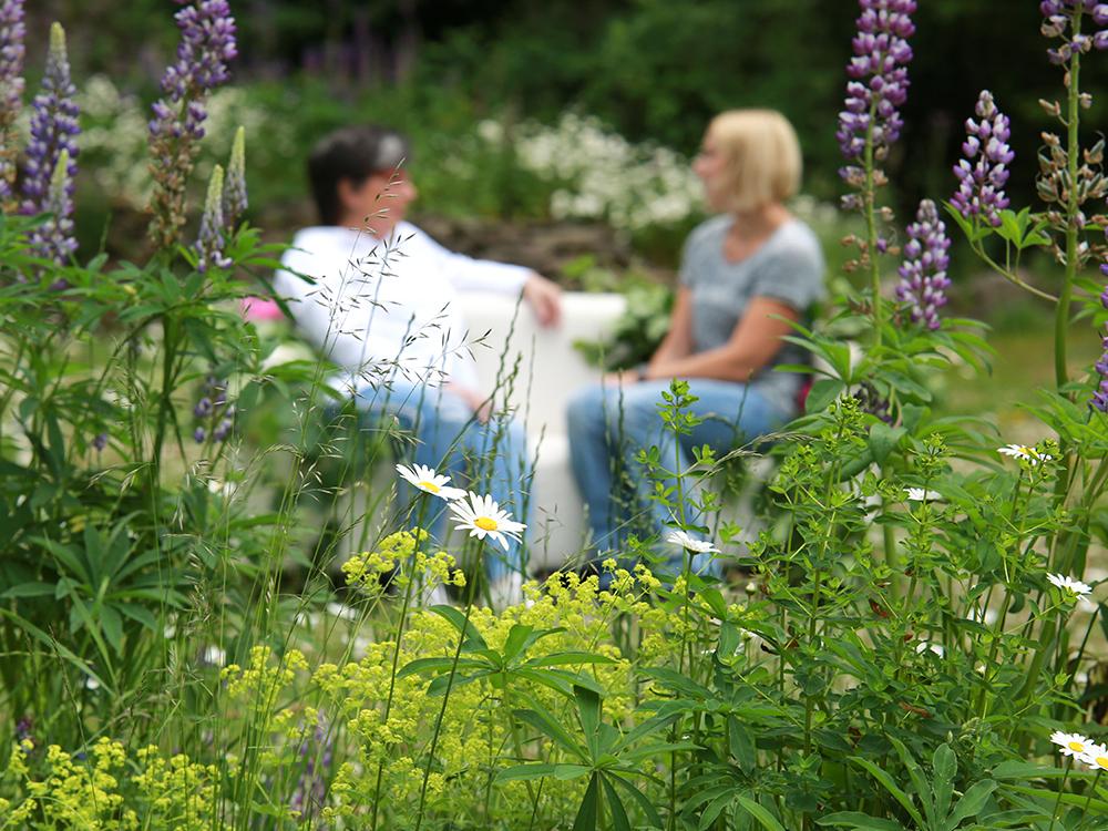 zwei Frauen sitzen in der Wiese zwischen Blumen und unterhalten sich