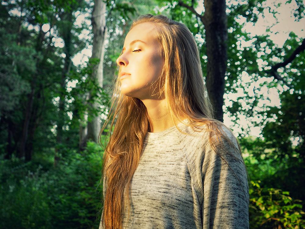 Frau in grauem Langarmshirt steht in der Nähe von grünen Bäumen während des Tages